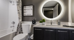 Our Tysons apartments feature light-infused bathrooms with oversized quartz vanities and natural tile accents.